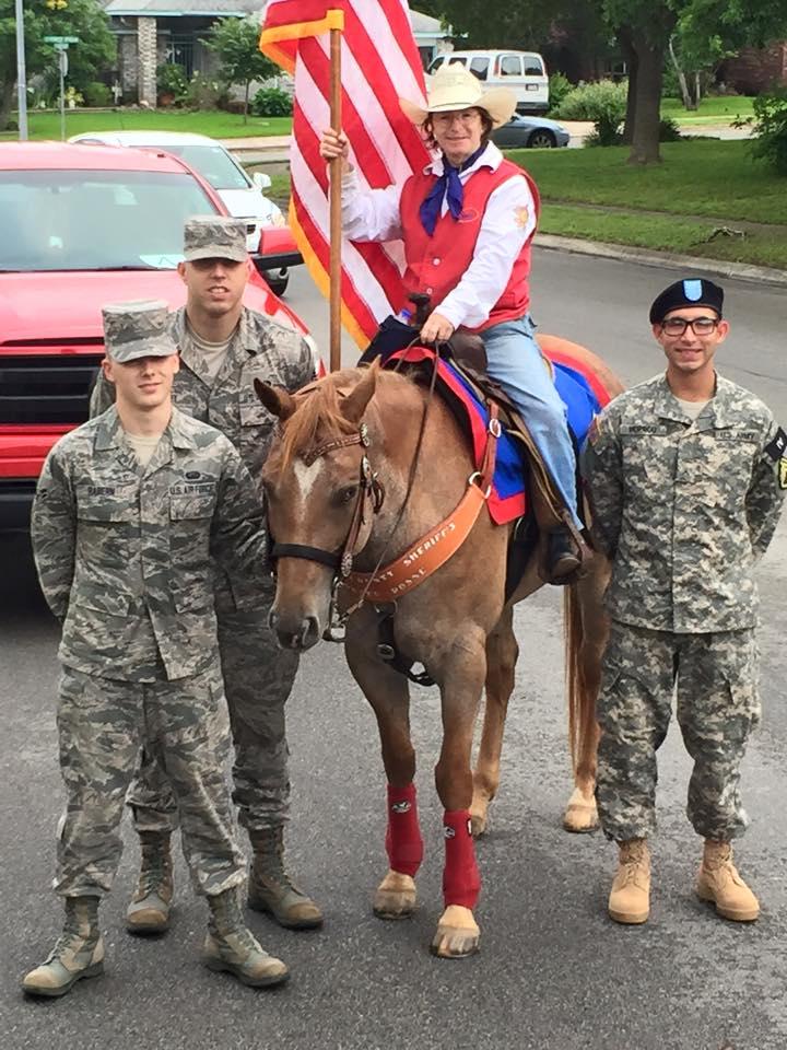 Linda Truax on horse beside three service men