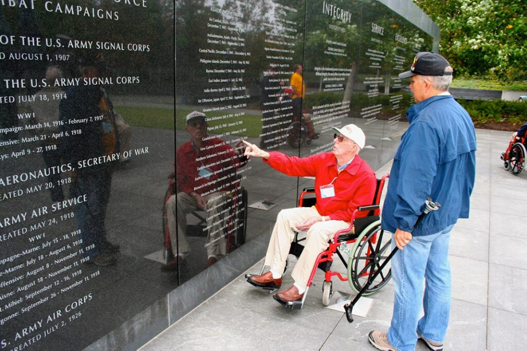 Two veterans looking at memorial wall