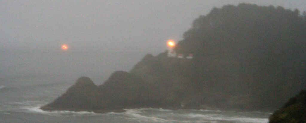 Lighthouse and boat in the fog